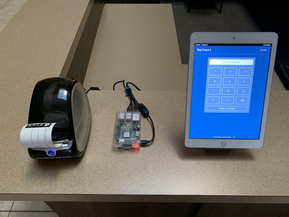 Dymo printer next to a Raspberry Pi computer and an iPad running Planning Center Check-Ins