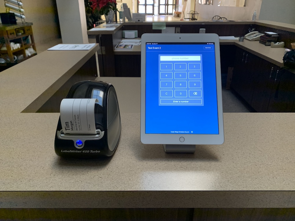 Dymo printer next to iPad running Planning Center Check-Ins
